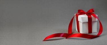 Bożenarodzeniowy prezent w Białym pudełku z Czerwonym faborkiem na zmroku Popielatym tle Nowego roku składu wakacyjny sztandar za zdjęcie stock