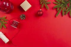 Bożenarodzeniowy prezenta opakowanie Jedlinowe gałąź, sosna rożki i teraźniejsi prezentów pudełka na czerwonym tle, fotografia stock