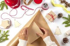 Bożenarodzeniowy prezenta opakowanie Kobiety ` s wręcza pakować Bożenarodzeniowej teraźniejszości pudełko w rzemiosło papierze obraz royalty free