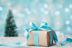Bożenarodzeniowy prezenta pudełko i zamazujący jedlinowy drzewo przeciw błękitnemu bokeh tłu 3d amerykanina karty kolorów wybuchu Obrazy Stock