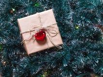 Bożenarodzeniowy prezenta pudełko na drzewa i girlandy tle Pakować wakacyjnych prezenty Obraz Royalty Free