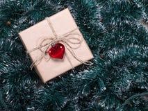 Bożenarodzeniowy prezenta pudełko na drzewa i girlandy tle Pakować wakacyjnych prezenty Obrazy Stock