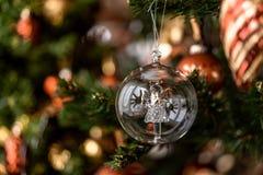 Bożenarodzeniowy przejrzysty balowy obwieszenie na sośnie rozgałęzia się z świątecznym tłem fotografia stock