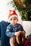 Bożenarodzeniowy rodzinny portret szczęśliwa uśmiechnięta chłopiec w czerwonym Santa kapeluszu w macierzystych ` s rękach Zima wa Zdjęcia Stock