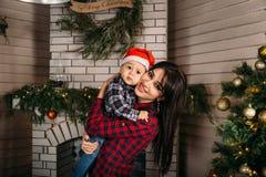 Bożenarodzeniowy rodzinny portret szczęśliwa uśmiechnięta chłopiec w czerwonym Santa kapeluszu w macierzystych ` s rękach Zima wa Zdjęcie Stock