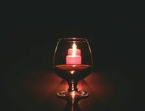 Bożenarodzeniowy skład fotografii koniaka szkło i świeczka na czarnym tle Zdjęcie Royalty Free