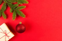 Bożenarodzeniowy skład na czerwonym tle Zielone jedlinowe gałąź, Xmas teraźniejszość pudełko, i dekoracja Zdjęcie Stock