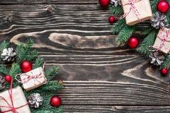 Bożenarodzeniowy skład robić jodeł gałąź, prezentów pudełka, dekoracje i sosna rożki, na nieociosanej drewnianej desce zdjęcia stock
