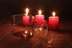 Bożenarodzeniowy skład z szklanym koniakiem, prezenta pudełkiem i świeczką na drewnianym stole, Obrazy Royalty Free