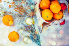 Bożenarodzeniowy skład z tangerines, cynamonem i jodłą, kapuje w drewnianym talerzu na świątecznym stole na zielonym tle z snowfl Zdjęcia Royalty Free