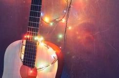 Bożenarodzeniowy tło, gitara akustyczna z girlandą, fotografia royalty free