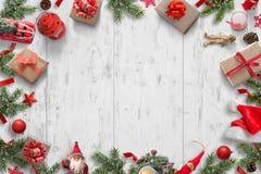 Bożenarodzeniowy tło na białym drewnianym biurku z choinką, prezenty, lale, piłki, Santa kapelusz, świeczki, lampion, pinecones Obraz Stock
