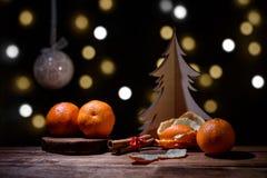 Bożenarodzeniowy tło - tangerines, cynamon, puchar, drewniany drzewo na zmroku z bokeh Fotografia Royalty Free