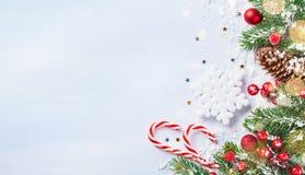 Bożenarodzeniowy tło z śnieżną jodłą rozgałęzia się, dekoracje, rożki i bokeh światła, Wakacyjny sztandar lub karta zdjęcia stock