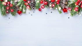 Bożenarodzeniowy tło z śnieżnymi jodeł gałąź, rożkami i bokeh światłami, Wakacyjny sztandar lub karta zdjęcia royalty free