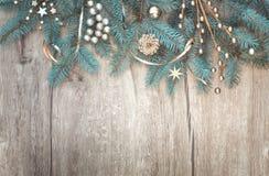 Bożenarodzeniowy tło z dekorującą jedlinową gałąź granicą na wo Fotografia Stock