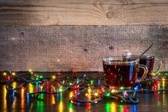 Bożenarodzeniowy tło z filiżankami herbata i światła na drewnianej teksturze Zdjęcie Royalty Free