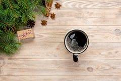 Bożenarodzeniowy tło z gorącą kawą, prezenta pudełko, jodła rozgałęzia się i konusuje na drewnianym stole, odgórnego widoku kopii obrazy stock