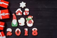 Bożenarodzeniowy tło z jedlinowym drzewem robić od piernikowych ciastek i czerwonych prezentów na drewnianym tle, kopii przestrze Fotografia Stock