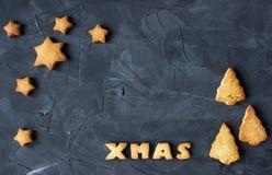 Bożenarodzeniowy tło z piec piernikowym słowa Xmas z gwiazdkowatym i choinką - kształtni ciastka kreatywnie Zdjęcie Royalty Free