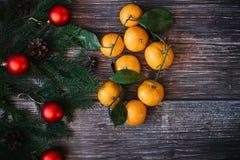 Bożenarodzeniowy tło z tangerines, jedlinowe gałąź, czerwone piłki Tradycyjny świąteczny zima wystrój dla nowego roku zdjęcie stock