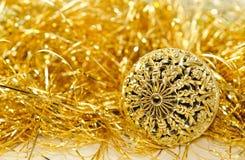 Bożenarodzeniowy tło z złotem rzeźbił balowego i złocistego świecidełko. Zdjęcie Stock
