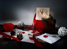 Bożenarodzeniowy tło z zegarem, śnieżnym jedlinowym drzewem i prezentów pudełkami nad drewnem, pisze list zaproszenia Święty Miko Obrazy Royalty Free