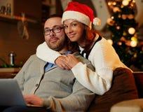 Bożenarodzeniowy wakacje Kobieta ściska mężczyzna używa laptop w Santa ` s kapeluszu Obraz Royalty Free