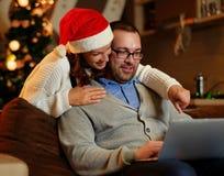Bożenarodzeniowy wakacje Kobieta ściska mężczyzna używa laptop w Santa ` s kapeluszu Obrazy Stock