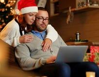 Bożenarodzeniowy wakacje Kobieta ściska mężczyzna używa laptop w Santa ` s kapeluszu Obrazy Royalty Free