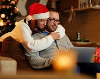 Bożenarodzeniowy wakacje Kobieta ściska mężczyzna używa laptop w Santa ` s kapeluszu Fotografia Royalty Free