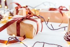 Bożenarodzeniowy wakacje skład z prezentami w rzemiosło papierze z atłasowym faborkiem na białym drewnianym tle z kopii przestrze Fotografia Stock
