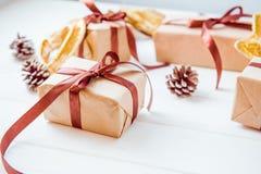 Bożenarodzeniowy wakacje skład z prezentami w rzemiosło papierze z atłasowym faborkiem na białym drewnianym tle z kopii przestrze Obraz Royalty Free