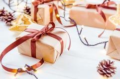 Bożenarodzeniowy wakacje skład z prezentami w rzemiosło papierze z atłasowym faborkiem na białym drewnianym tle z kopii przestrze Obrazy Royalty Free