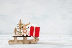 Bożenarodzeniowy wakacyjny świąteczny temat z drewnianym ślicznym reniferem na saniu, czerwoni prezentów pudełka na białym nieoci zdjęcie royalty free