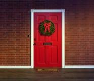 Bożenarodzeniowy wianek na czerwonym dzwi wejściowy z mile widziany matą Zdjęcia Royalty Free
