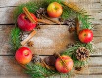 Bożenarodzeniowy wianek robić jodeł gałąź, rożki, czerwoni jabłka Fotografia Stock