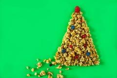 Bożenarodzeniowy zdrowy styl życia układu granola lub muesli w kształcie choinka z piłkami jagody i malinki na wierzchołku dalej obrazy stock