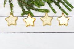 Bożenarodzeniowych dekoracj złoci sprockets na białym drewnianym backgroun Obrazy Stock
