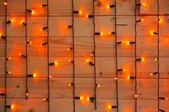 Bożonarodzeniowe światła na ścianie drewniane deski. Obrazy Royalty Free