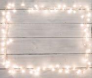 Bożonarodzeniowe światła na bielu malowali drewnianego tło z kopii sp Obraz Stock