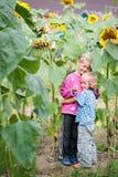 Bo den lyckliga barnsyskongruppen i busksnåren av solrosen i trädgården av lantgården royaltyfri bild