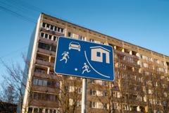 Bo det europeiska vägmärket för sektor i Riga, Lettland med en typisk sovjetisk flerbostadshushusbyggnad i bakgrunden fotografering för bildbyråer