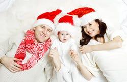 Bożenarodzeniowa rodzina z dzieckiem w czerwonych kapeluszach. Fotografia Royalty Free