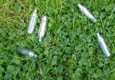 Bo?tes m?talliques jet?es de gaz hilarant dans l'herbe : fioles en m?tal contenant le gaz de protoxyde d'azote, utilis? pour la c image stock