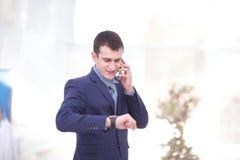 Boa conversa do negócio Homem novo considerável no formalwear que fala no telefone e que sorri ao sentar-se na mesa de escritório Foto de Stock