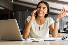 Boa conversa do negócio Mulher bonita nova alegre que fala no telefone celular e que usa o portátil com sorriso ao sentar-se em imagens de stock royalty free