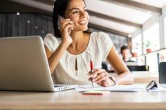 Boa conversa do negócio Mulher bonita nova alegre que fala no telefone celular e que usa o portátil com sorriso ao sentar-se em fotografia de stock