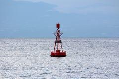 Boa della navigazione rossa con luce sui pannelli solari superiori e piccoli per l'incarico circondati del mare agitato fotografie stock