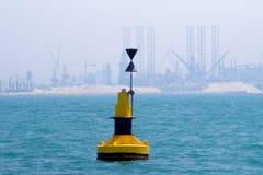 Boa di navigazione all'entrata di un canale Industria marina del gas e del petrolio come fondo: Martinetti, impianti di perforazi immagine stock